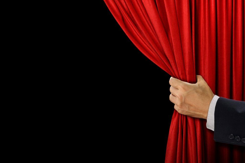 Hand open stage red curtain on black background