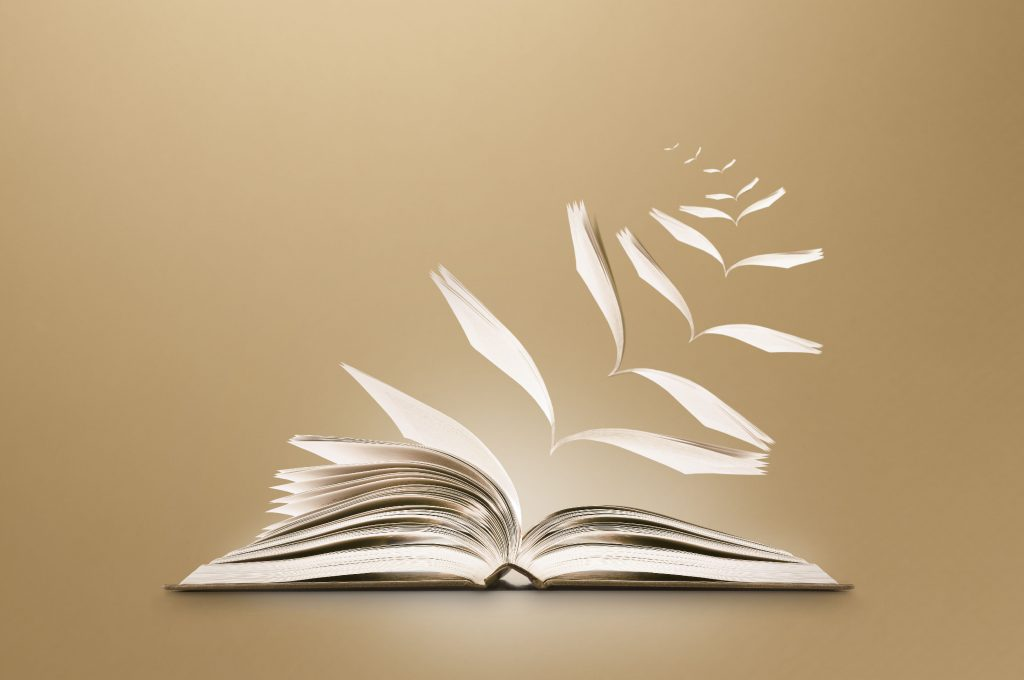 conceptual image of a reading book opening and pages flying away as if imagined in a story, on a subtle brown background with extended areas for copy space